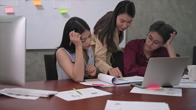 若いアジアの女性チームの行動は疲れている、満足のいくものではなく、オフィスでの仕事の議論の後に仕事に飽きた - 不安点の映像素材/bロール