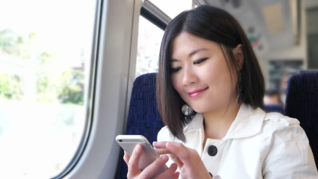 Young Asian woman text messaging on a train.