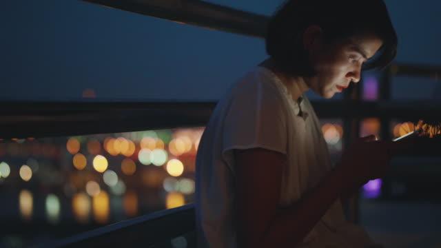 夜、彼の携帯電話上に若いアジア女性テキスト メッセージ - 30代の女性一人点の映像素材/bロール
