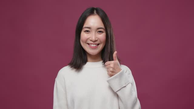 junge asiatische frau daumen nach oben geste gegen marsala copyspace - anmut stock-videos und b-roll-filmmaterial