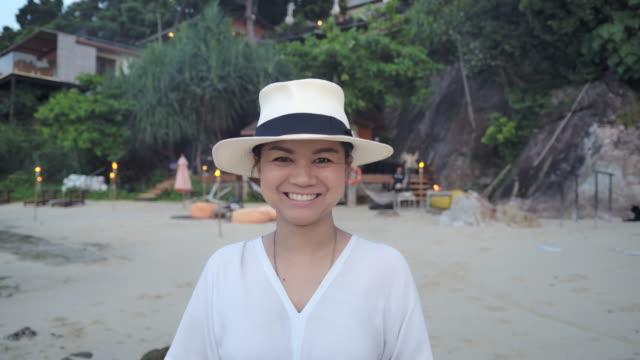 eine junge asiatische touristin im weißen kleid und einem weißen hut lächelt und genießt ihren urlaub in der strand-tagesszene - weißes kleid stock-videos und b-roll-filmmaterial