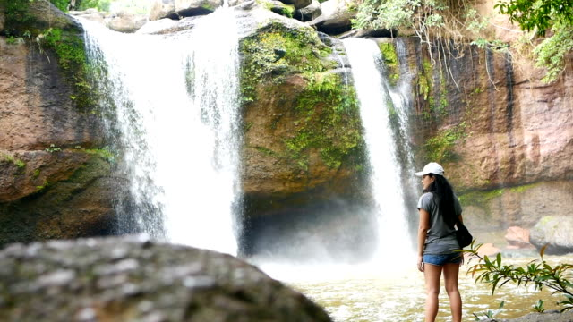 Young Asian woman traveler standing in front of waterfall