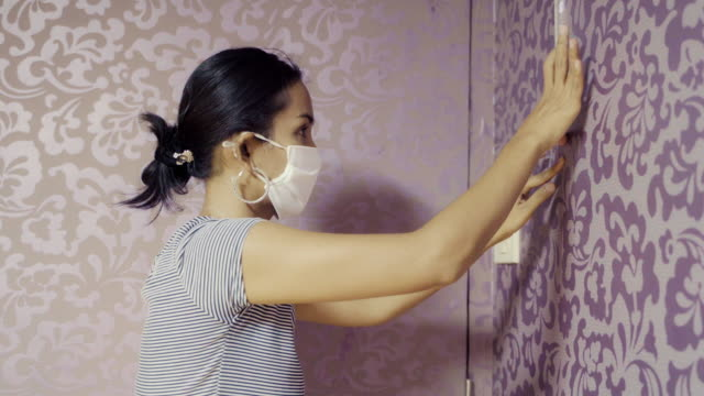 vídeos de stock e filmes b-roll de young asian woman try to glueing and fixing wallpaper with herself and face mask protection. do the chore concept. - papel de parede