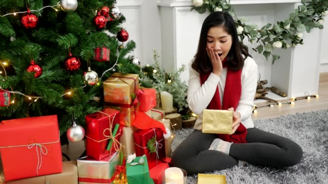 young asian woman unpacking christmas present celebrate christmas in living room at home in christmas festival. lifestyle beautiful happy women celebrate festival concept. - unwrapped present stock videos and b-roll footage