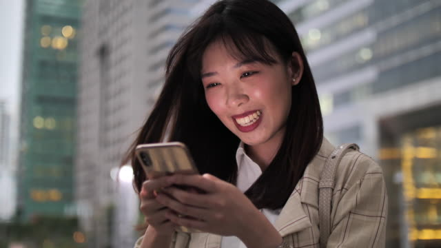 young asian woman uses smartphone while standing in city view - only young women stock videos & royalty-free footage