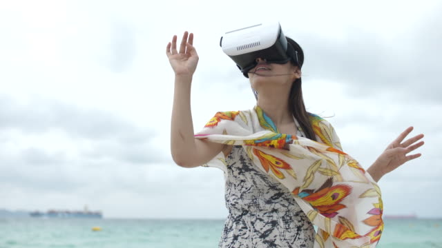Young Asian woman using 3d virtual reality googles on beach, Slow motion