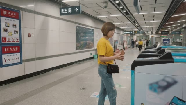 young asian woman using app device on smartphone to pay for subway ride - tapping stock videos & royalty-free footage