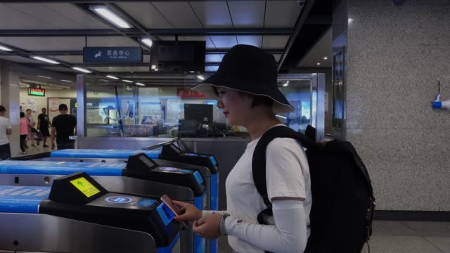 young asian woman using app device on smartphone to pay for subway ride,xi'an,china. - tapping stock videos & royalty-free footage