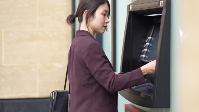 young asian woman using atm in city - three quarter length stock videos & royalty-free footage