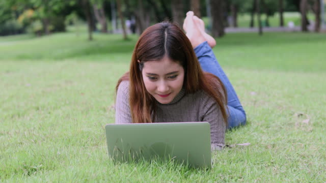 young asian woman using computer outdoor - east asian ethnicity video stock e b–roll