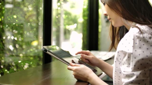 stockvideo's en b-roll-footage met jonge aziatische vrouw met behulp van digitale tablet - exclusief