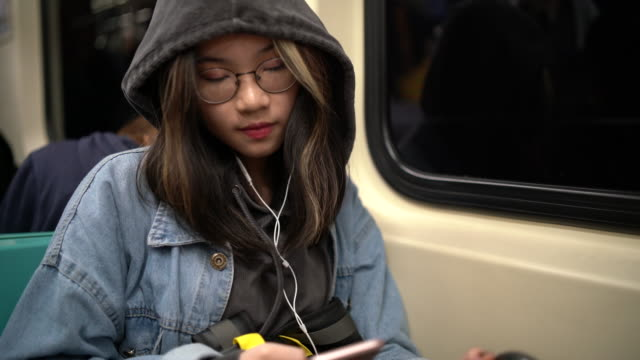 young asian woman using her smartphone in a metro train - public transportation stock videos & royalty-free footage