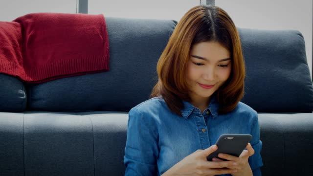 vidéos et rushes de jeune femme asiatique avec gsm et souriant tout en étant assis sur le sol à la maison - living room