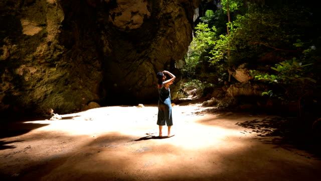 Young Asian woman using mobile phone touchscreen take a photo at Phraya Nakorn cave, Thailand