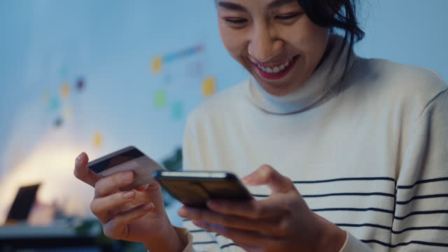 young asian woman using mobile phone while performing online transactions with credit card during shopping sitting on sofa at home at night. - electronic banking stock videos & royalty-free footage