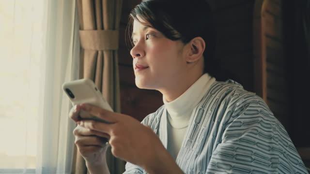 自宅で現代のスマートフォンデバイスを使用して若いアジアの女性。 - 家の中点の映像素材/bロール