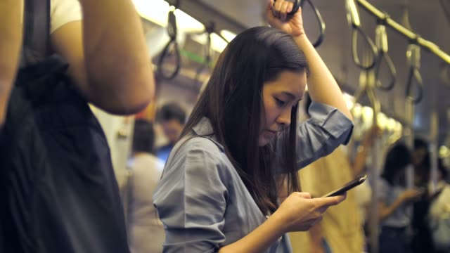 young asian woman using phone at metro - rail transportation stock videos & royalty-free footage