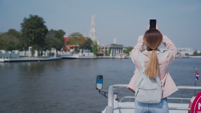 young asian woman using phone calling to her friend on tour boat - local landmark stock videos & royalty-free footage