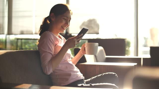 vídeos de stock, filmes e b-roll de jovem asiática usando telefone inteligente em café - portable information device