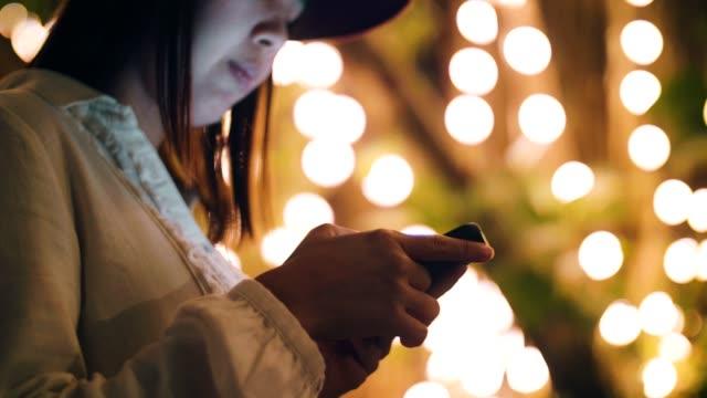 junge asiatin mit smartphone in der nacht - menschlicher finger stock-videos und b-roll-filmmaterial