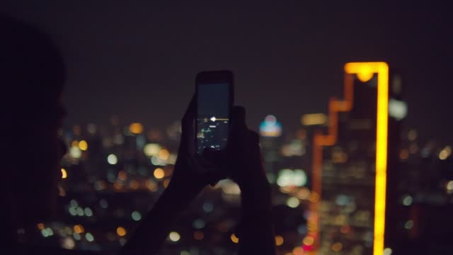young asian woman using smart phone with beautiful bokeh in the city at night - standing stock videos & royalty-free footage