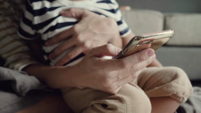 vidéos et rushes de jeune femme asiatique à l'aide de smartphone dans la maison avec son bébé - prendre sur les genoux