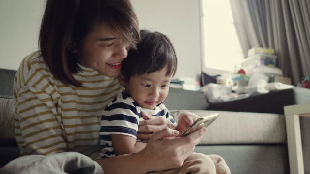 Young asian woman using smartphone in home with her baby