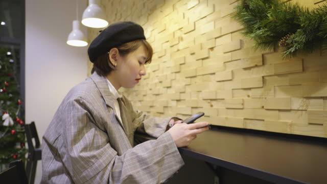 vídeos y material grabado en eventos de stock de joven asiática usando el teléfono inteligente para comprar en línea en navidad, día de año nuevo - sólo una adolescente