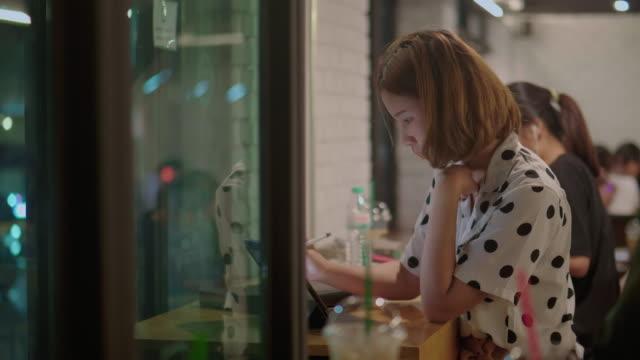 junge asiatische frau mit tablet in der nacht in woke space coffee shop - schale stock-videos und b-roll-filmmaterial