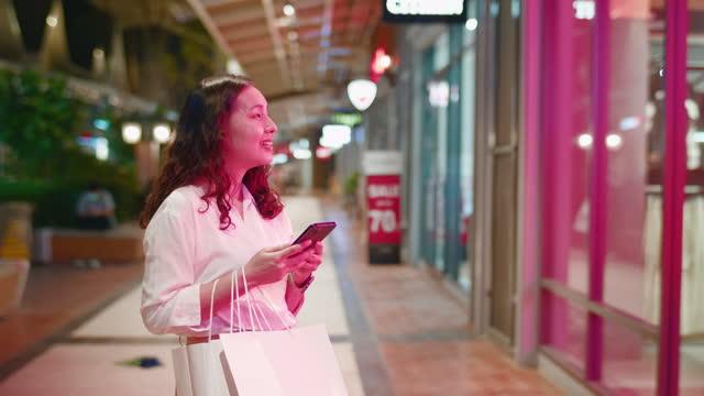 vídeos de stock e filmes b-roll de young asian woman using the phone and looking at shop window store - viciado em compras