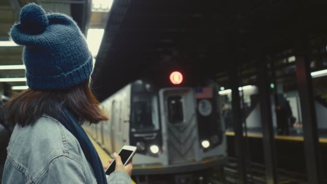 young asian woman waiting and texting with cell phones on subway platform. - hat stock videos & royalty-free footage