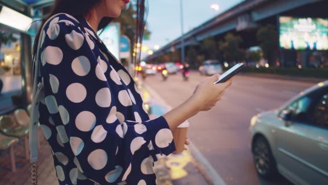 junge asiatische frau wartet auf taxi in bangkok stadt. - straßenrand stock-videos und b-roll-filmmaterial