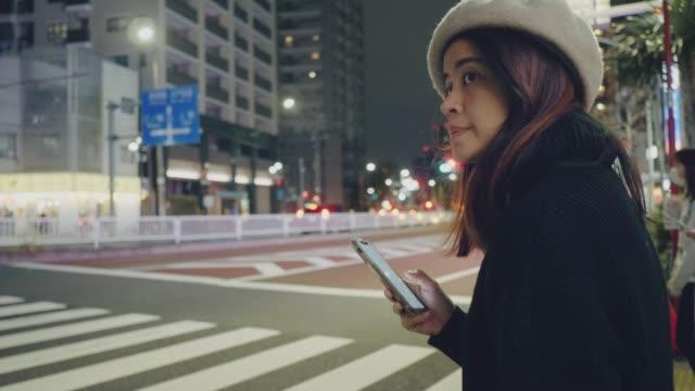 vidéos et rushes de jeune femme asiatique attendant le taxi dans la ville de tokyo. - traverser