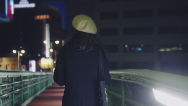 young asian woman walking and using his smartphone at night. - zona pedonale strada transitabile video stock e b–roll