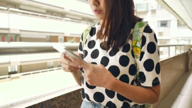 vídeos de stock e filmes b-roll de young asian woman walking and using touchscreen technology at smartphone. - arrendamento de casa