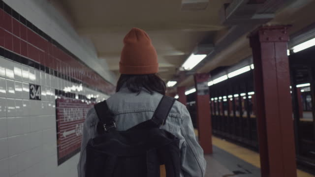 young asian woman walking on subway platform. - vita cittadina video stock e b–roll
