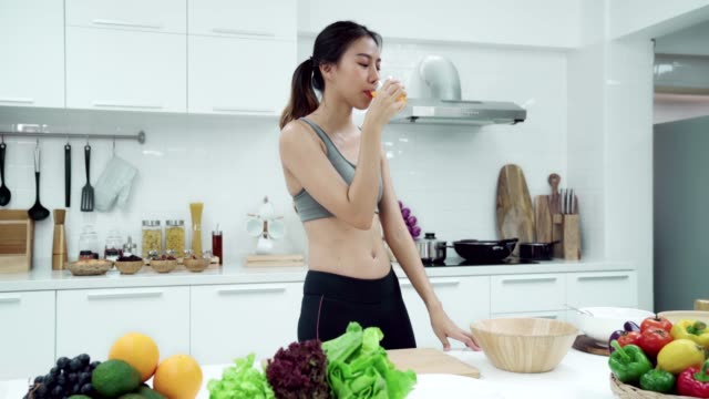 young asian woman walking to kitchen home and drinking orange juice in moring weekend day. healthy eating and healthy lifestyle concept. - chores stock videos & royalty-free footage