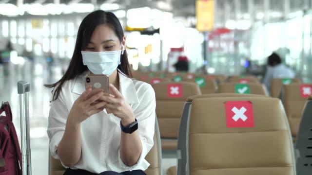 junge asiatische frau tragen schützende gesichtsmaske mit smartphone am flughafen sitzen warten in neuen raum soziale abstand - geschäftsreise stock-videos und b-roll-filmmaterial
