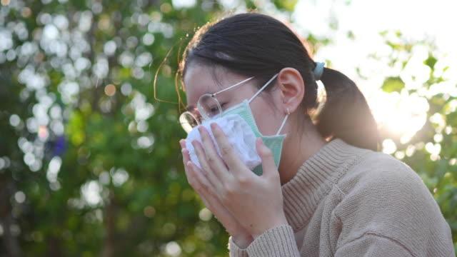 junge asiatische frau trägt eine schützende gesichtsmaske, um die ausbreitung von coronavirus zu verhindern, ein globaler gesundheitsnotfall covid-19 - menschlicher finger stock-videos und b-roll-filmmaterial