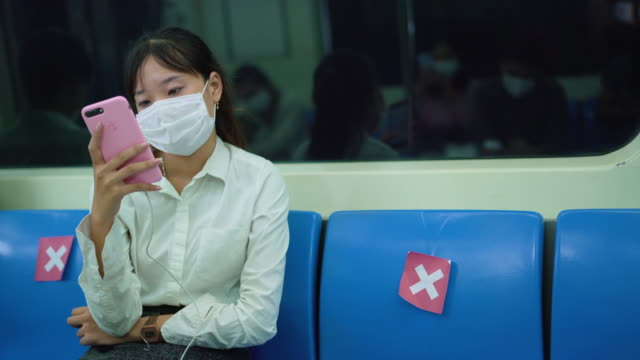 young asian woman wearing a surgical mask is using smart phone in the subway train - public transport stock videos & royalty-free footage