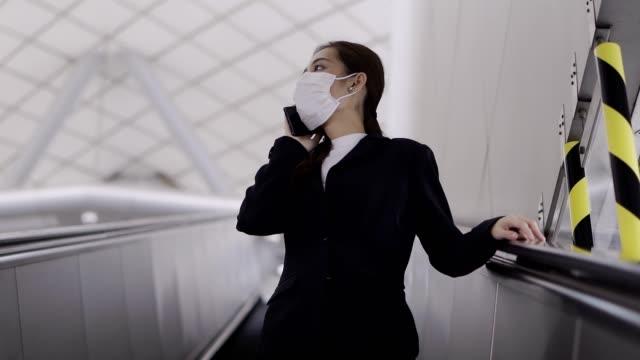 junge asiatische frau trägt eine weiße chirurgische gesichtsmaske und mit handy in u-bahn-zug während des neuen typs coronavirus covid-19 - biomedical illustration stock-videos und b-roll-filmmaterial