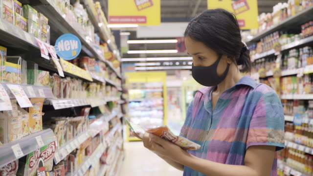 young asian woman wearing face mask to protect from virus or illness and buying in supermarket. - unhealthy living stock videos & royalty-free footage
