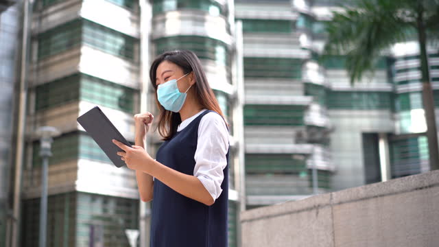 young asian woman wearing protective face mask and using digital tablet outdoor - petronas twin towers stock videos & royalty-free footage