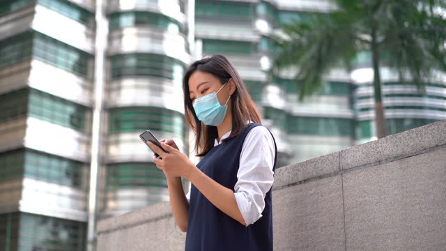 young asian woman wearing protective face mask and using smartphone - petronas twin towers stock videos & royalty-free footage