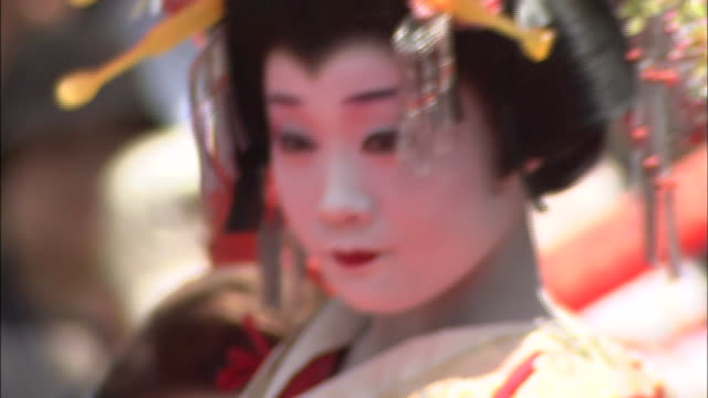 a young asian woman wears traditional face makeup and court attire as she performs a ceremonial dance during the sentei festival in shimonoseki, japan. - tradition stock videos & royalty-free footage