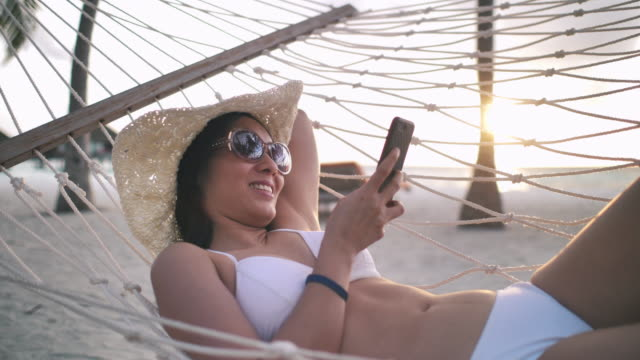 ung asiatisk kvinna med en hatt och hörlurar, liggande i hängmattan på stranden, med hjälp av sin smartphone, - hängmatta sol bildbanksvideor och videomaterial från bakom kulisserna