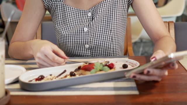 Ung asiatisk kvinna med vackert leende njuta av att äta choklad kaka dessert på kafé och snacka med mobiltelefon för online-verksamhet