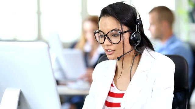 vidéos et rushes de femme asiatique hd young avec casque et lunettes de vue à l'aide d'ordinateur et de parler au bureau moderne - équipement audiovisuel