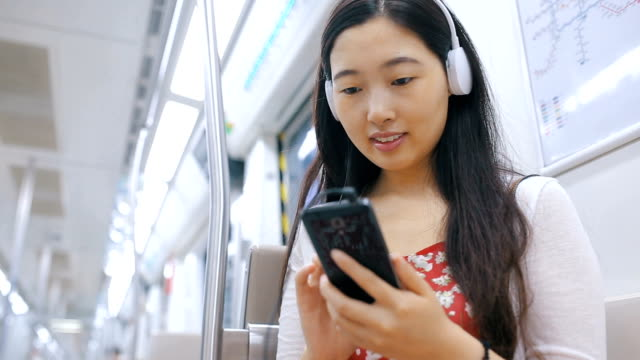 young asian woman with mobile phone in subway - 動画関連点の映像素材/bロール