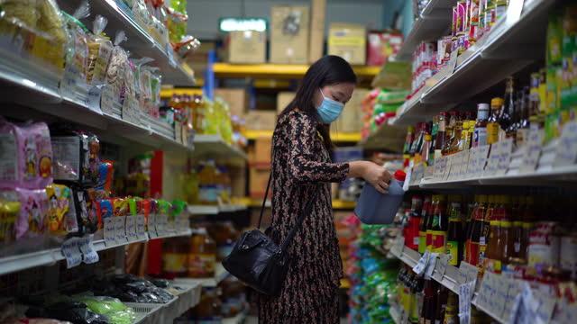 stockvideo's en b-roll-footage met jonge aziatische vrouw met beschermend gezichtsmasker dat voor kruidenierswaren bij supermarkt winkelt - maleisië